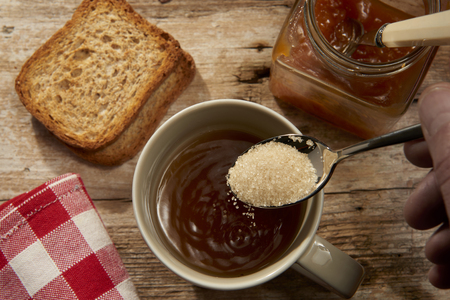 pouring brown sugar into a cup of hot tea with jam and bread