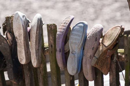 Old worn house slippers on wooden fence. Symbol of poor. the concept of poverty Reklamní fotografie