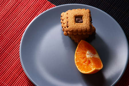 chocolate chip cookies and orange on gray plate and on red with black table Stock Photo