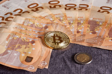 Studio shot of bitcoin physical golden coin on 50 euro bills banknotes Stock Photo