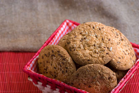 Savory cookies sprinkled with sesame seeds, sunflower on a wooden table and burlap background