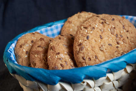 homemade oat cookies with sunflower seeds in and near blue checkered basket on black wooden background