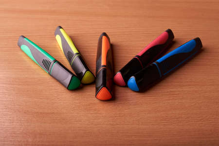 colored markers on the school table on wooden background