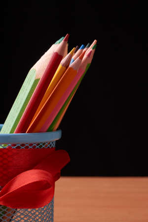 color pencils in tin can on wood table on black