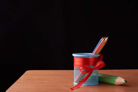 color pencils in tin can with big green pencils on wood table on black Stock Photo