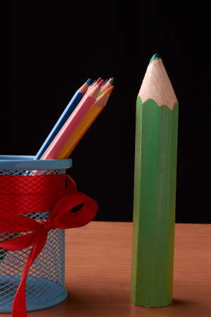 color pencils in tin can with big green pencils on wood table on black 写真素材