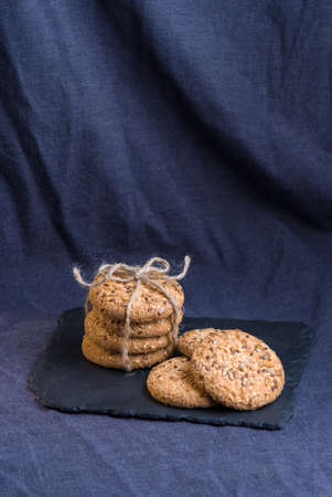 homemade oat cookies with sunflower seeds on shale board and dark blue background Stock Photo