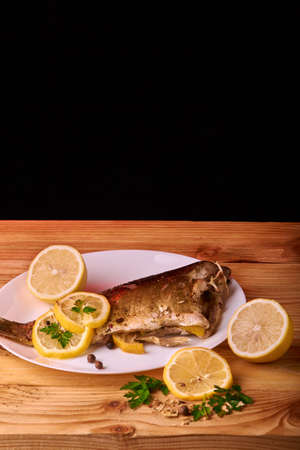 On a wooden table plate with roasted carp fish dorado with parsley, chives and lemon