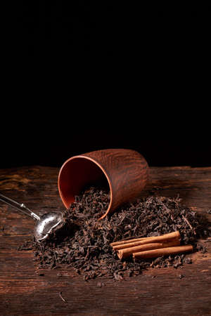 Picture of the tea strainer with dried tea leaves and sticks of cinnamon on darck wooden background