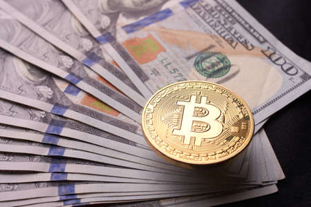 Beautifully arranged bills 100 dollar and gold coin bitcoin on a gray background. Bitcoin cryptocurrency.