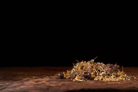 Herbal tea on wooden table on black background