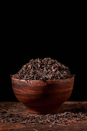 Dry tea leaves in clay bowl on black background on wooden table