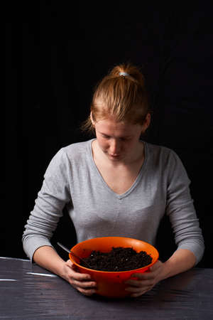 Close up young woman preparing ground for planting on table