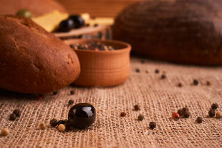 fresh bread baguette with olive oil, olives. cheese and rosemary on wooden background Banque d'images