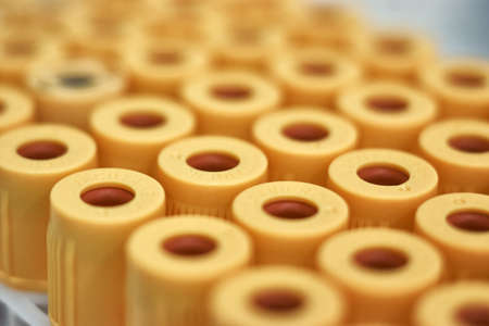 macro of test tubes with yellow top, against a gradient of white background