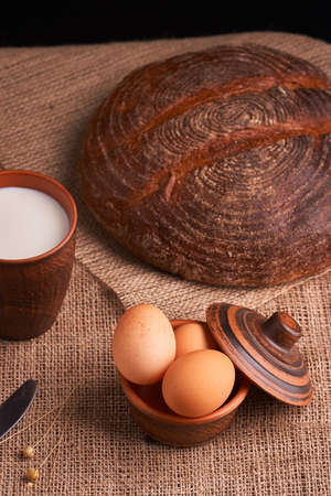 Eggs with bread and kitchen utensils on vintage wooden background 免版税图像