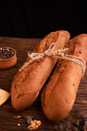 Two Fresh baguettes on dark wooden table Stock Photo