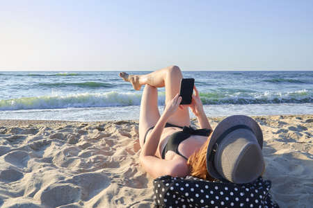 Beautiful woman lying on the beach and looking at the smartphone