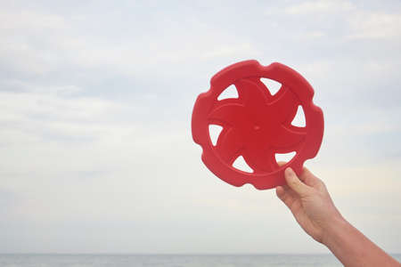 flying disk in hands on the beach