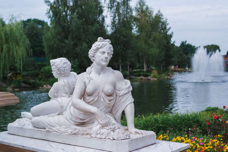 Ancient women statue in lake background. Statue in park