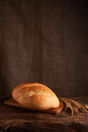 Bakery - gold rustic crusty loaves of bread and buns on black chalkboard background Stock Photo