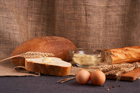 Different bread and wheat on the rustic table. Selective focus