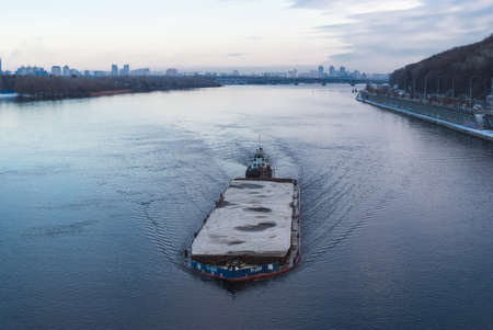 The barge floating in the Dnieper river. Kyiv city landscape in the background.