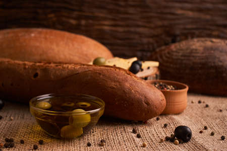 Fresh Italian baguette on wooden table with oil.Selective focus Stock Photo