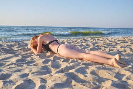 Positive and serene young woman sunbathing at seaside with closed eyes.