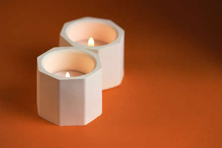 burning candle in a concrete candle holder on orange background