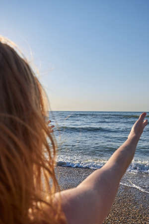 Woman looking to the sea ocean from the back naked with windy hair