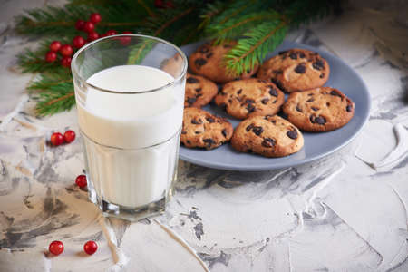 holidays, celebration and home concept - milk and cookies for Santa