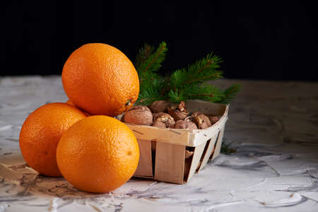 nuts on the wooden basket and oranges on white background. healthy new year s breakfast. Imagens