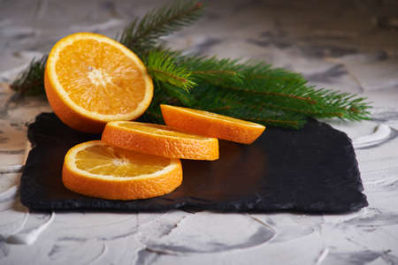Fresh slised oranges on the gray background and with spruce branch Imagens