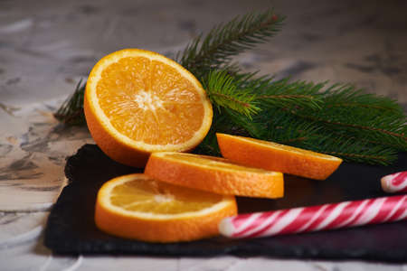 Fresh slised oranges on the gray background and with spruce branch and with candy