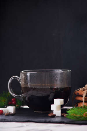 Coffee with milk preparation in glass cup with coffee beans and sugar on black background