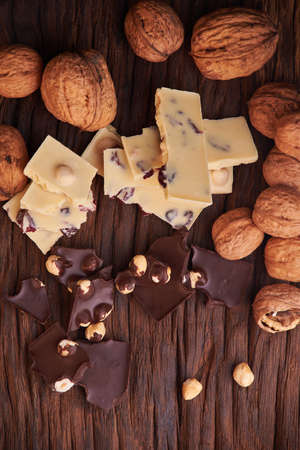 Nuts and milk and dark chocolate pieces on wooden background. Tasty and sweet food