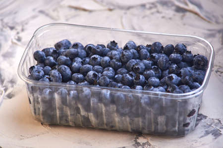 Blueberries in a plastic can on old rustic wooden table Imagens