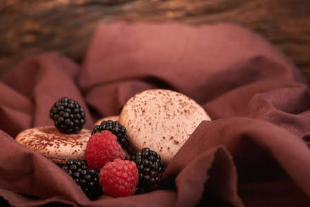 chocolate Macaroons and blackberries and raspberries on the table Imagens