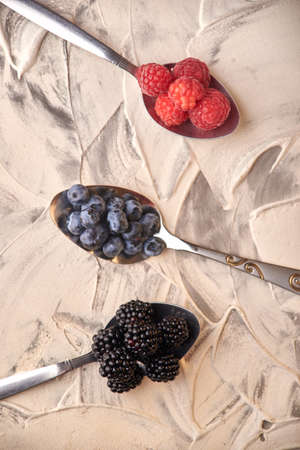 mix of fresh delicious berries lying on spoons