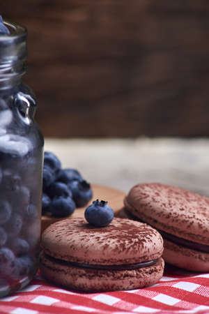 Fresh and tasty blueberry berries in a glass jar with sweet macaroons on a checkered napkin