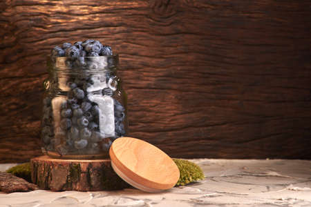 fresh and tasty blueberry berries in a glass jar and with a checkered napkin Imagens