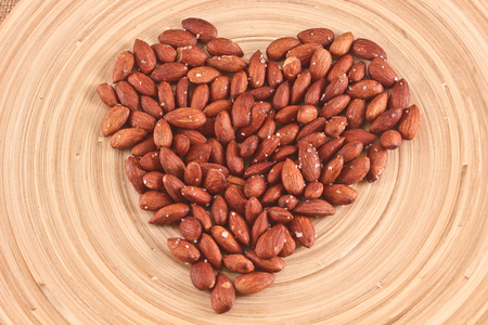 Salted Roasted Almonds Nuts on Wooden Surface photo