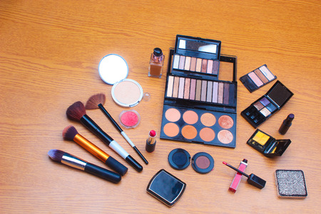 eyemakeup: Makeup Palettes and Cosmetics Professional Brushes on a Wooden Background  Makeup Palettes and Cosmetics Professional Brushes  Makeup Splash Stock Photo