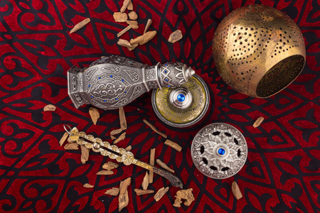 Silver Oriental Artistic Arabian Oud Perfume  Arabian Oud Perfume with Oud Scented Wood burned in the background with Scented Smoke in the Air