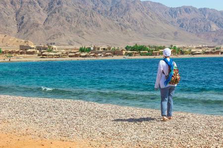 monte sinai: Joven dama de pie junto a la cabaña en un campamento en el desierto de Sinaí, Taba con el fondo del mar y las montañas.