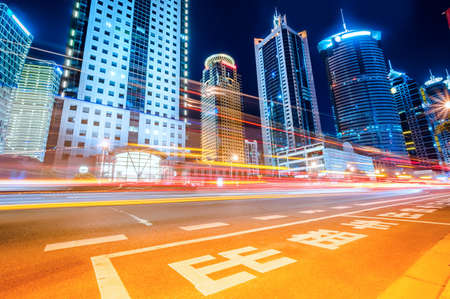 The light trails on the modern building background in shanghai china. Stock fotó