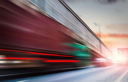 fast delivery: truck speeding through a bridge at sunset,motion blur.