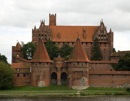 opposite: Malbork castle entrance from opposite river bank Stock Photo