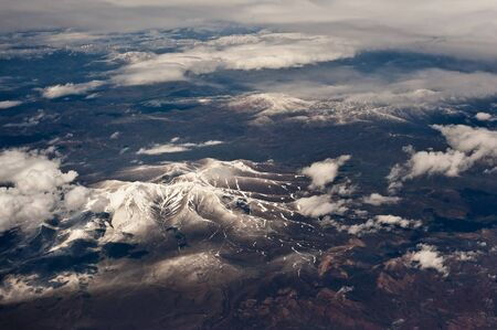 Aerial photography of snowy mountains covered with clouds photo